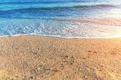 接近的沙子海滩和波浪在有灼烧的太阳的希腊 库存照片