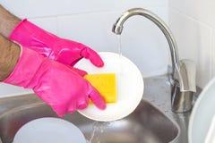 接近的洗碗 在泡沫的男性手在房子的厨房里洗涤与洗涤剂的陶器和海绵 免版税库存图片