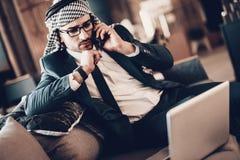 接近的照片阿拉伯谈话在长沙发的电话 库存照片