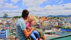 接近的父亲小女孩坐屋顶波浪手神色在城市 股票录像