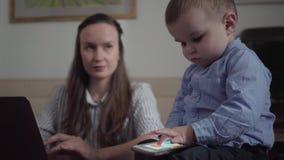 接近的画象年轻母亲女实业家工作在与膝上型计算机的办公室桌上的和可爱的男婴坐 股票录像