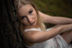 接近的画象-在白色礼服的美丽的幼小白肤金发的妇女森林若虫在常青木头 免版税库存图片