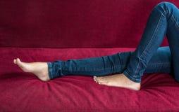 接近的穿牛仔裤的赤足妇女和腿在红色沙发在家气喘作为放松和休息在假日 r 库存图片