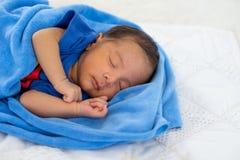 接近的观点的亚裔年轻新生儿与在白色床上的蓝色毛巾睡觉在有柔光的卧室 库存图片