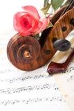 接近的观点的小提琴纸卷、弓和红色玫瑰 库存图片