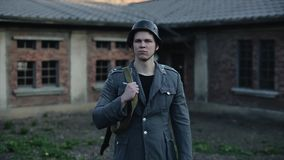 接近的观点的有一个被弄脏的历史大厦的一名普通的德国士兵在背景中 朝右边看 股票录像