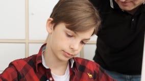 接近的观点的红色T恤杉的欧洲男孩解释他从任务的自己的差错到他的父亲慢动作 股票录像
