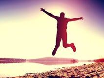 接近的跳的人射击了 运动员疯狂跳跃和跑步在海滩在日出期间 免版税库存照片