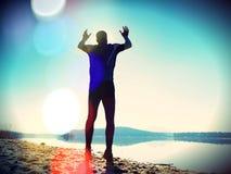 接近的跳的人射击了 运动员疯狂跳跃和跑步在海滩在日出期间 库存图片