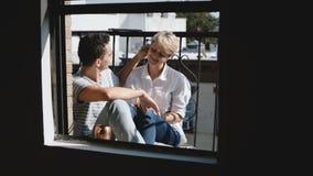 接近美好的年轻浪漫夫妇的照相机靠近坐,拥抱和谈话在一个小晴朗的阳台 股票录像