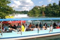 接近莱茵河瀑布的一个游船的人们 库存照片
