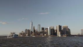 接近财政摩天大楼的小船在街市纽约在从黄昏的河摄制的更低的曼哈顿 股票录像