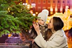 接近绿色圣诞树的微笑的家庭 免版税库存照片