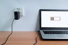 接通电源输出口适配器在手提电脑的白色墙壁上的绳子充电器在木的 免版税图库摄影