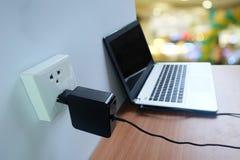 接通电源输出口适配器在手提电脑的白色墙壁上的绳子充电器在木的 库存照片