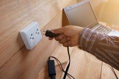 接通适配器便携式计算机电源线充电器在木地板上的 免版税库存图片