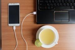 接通USB手机的绳子充电器有膝上型计算机和新近地柠檬汁的在一个白色杯子,在木地板上 库存照片