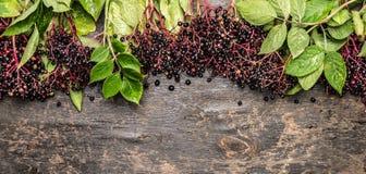 接骨木浆果捆成一束与在土气木背景,顶视图的绿色叶子 免版税库存照片