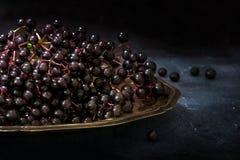 黑接骨木浆果& x28; 接骨木花nigra& x29;在一个老银盘上,黑暗 库存图片