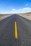 直接死亡谷路横跨山的沙漠 库存照片