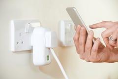 控制巧妙的插座的妇女使用在手机的App 库存图片