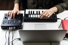 控制或混合在计算机上的男性收养电子音乐轨道在现代作用处理器帮助下  免版税库存图片