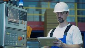 控制板和站立在它旁边的一位男性技术员与片剂 股票视频