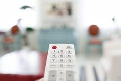 控制查出的遥控 交换在电视键盘的节目 明亮的客厅 早晨欧洲人家 免版税图库摄影