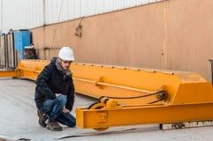 控制桥式起重机的年轻工程师在工厂 免版税库存图片