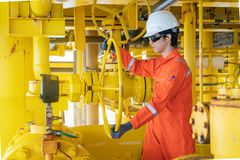 控制气体和原油产品的近海油和煤气站点服务操作员开放阀门在中央处理平台 库存照片