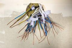 推出从在白色墙壁上的插口的电子被暴露的被连接的导线 电子架线的设施 完成的工作  免版税图库摄影