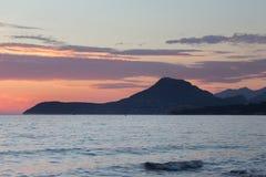 推出从有橙色天空的海的山 库存照片