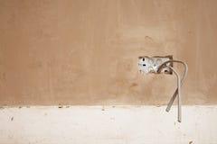 推出从涂灰泥的墙壁的导线 库存照片