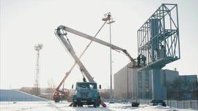 推力桶的工作者在恶劣天气的设施大广告牌期间 工作者安装一个广告牌 工作者和推力 股票录像