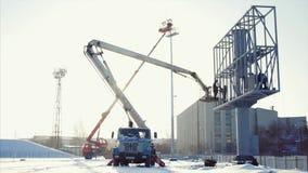 推力桶的工作者在恶劣天气的设施大广告牌期间 工作者安装一个广告牌 工作者和推力 影视素材