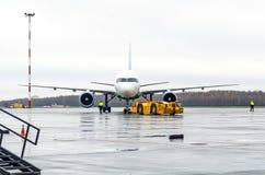 推回飞机的拖车对停车场在机场 免版税库存图片