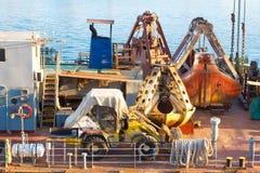 推土机和货物起重机生锈的瓢在船甲板的 免版税库存照片
