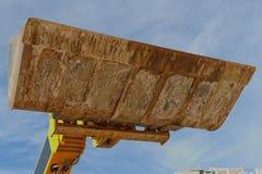 推土机在天空背景的挖掘瓢 免版税库存图片