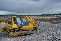 推土机移动在建造场所的石渣 库存照片