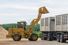 推土机装货沙子到卡车里 库存照片