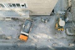 推土机装载者上载的废物和残骸到翻斗车里在工地工作 大厦折除和建筑 免版税库存照片