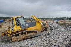 推土机移动在建造场所的石渣 免版税库存照片