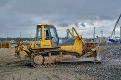 推土机移动在建造场所的石渣 免版税库存图片