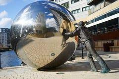 推挤一个大镜子球的一个人的雕象 免版税图库摄影