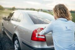 推挤一辆残破的汽车,人司机的妇女 免版税库存照片
