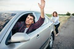 推挤一辆残破的汽车,人司机的妇女 库存图片