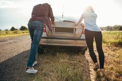 推挤一辆残破的汽车,后面看法的男人和妇女 免版税库存照片