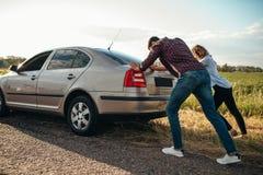 推挤一辆残破的汽车,后面看法的男人和妇女 库存图片