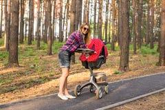 推挤一辆婴儿推车的全长年轻母亲在公园 库存图片