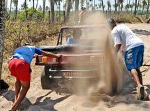 推挤儿童车的两个人在沙子阻塞了 库存图片